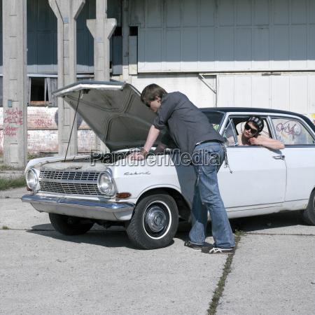 junger mann untersucht auto waehrend frau