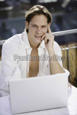 young man using laptop on balcony