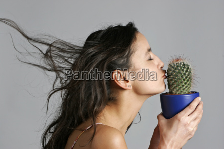 young woman kissing cactus close up