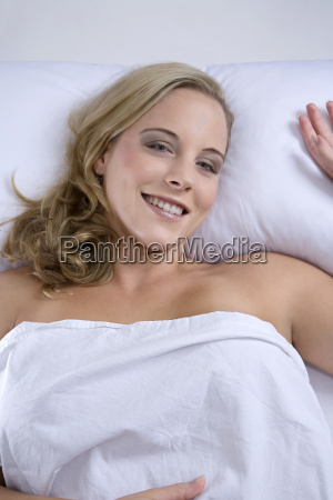 young blonde woman lying on bed