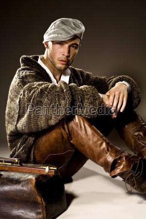 junger mann mit lederhose und cardigan