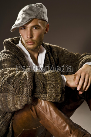 junger mann traegt lederhose und strickjacke