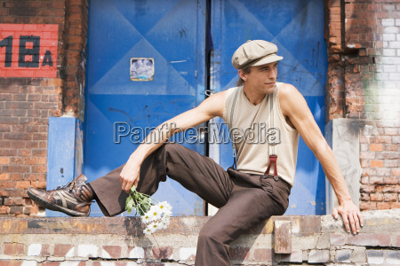 young man sitting on brick wall