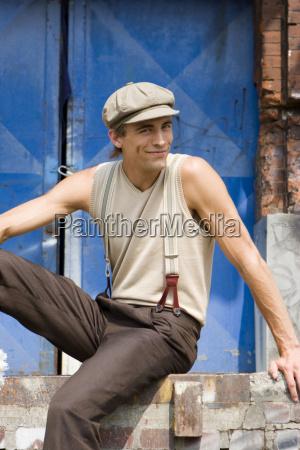 young man sitting on brick wall