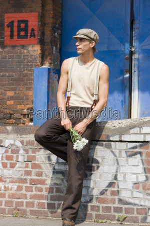 young man holding bunch of flowers