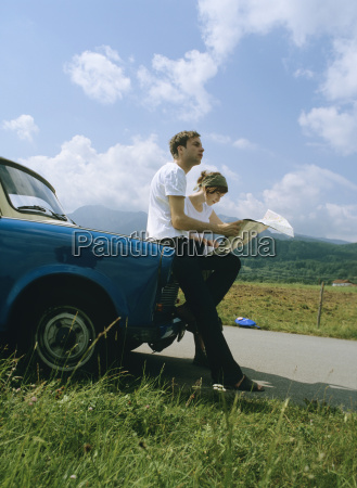 couple with map leaning on car