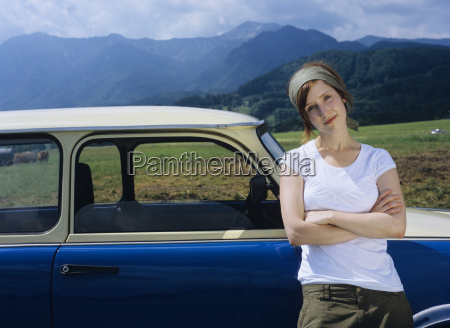 young woman leaning on car