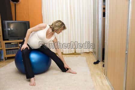 schwangere frau die auf gymnastikball sitzt