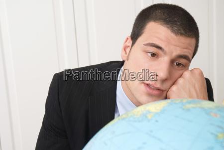 businessman looking at globe close up