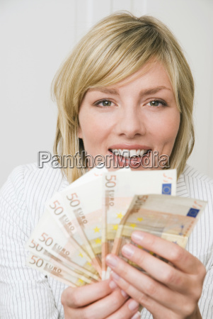 woman holding 50 euro notes smiling