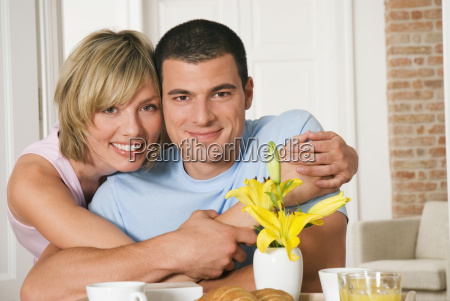 young couple hugging at breakfast table