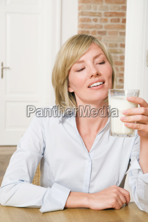 young woman holding glass of milk