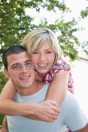 couple woman embracing man from behind