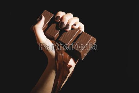 female hand holding melting chocolate bar