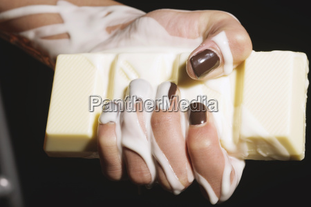 female hand holding melting chocolate bar