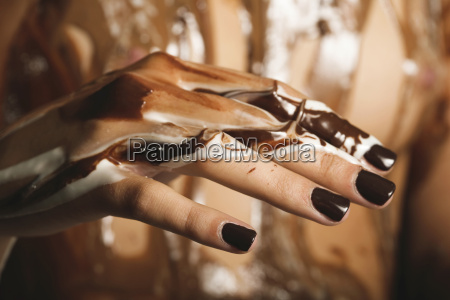 female hand with melted chocolate close