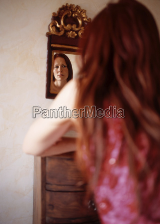 red haired woman looking in mirror