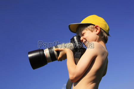 boy 10 12 holding camera