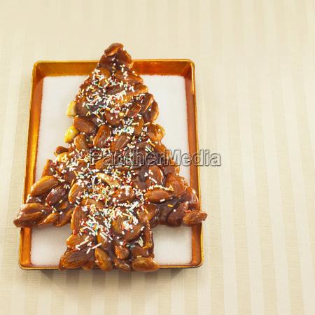 weihnachtlich baumfoermige mandelkekse auf tablett nahaufnahme