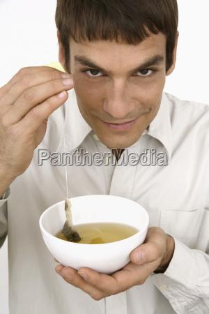 man holding tea bowl close up