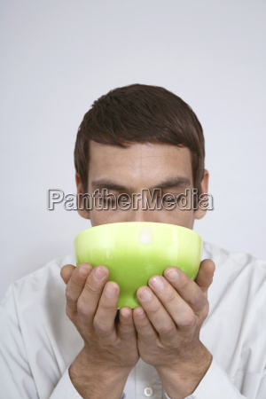man holding tea bowl close up