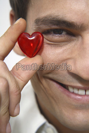 man holding red heart close up