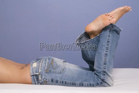 frau auf dem bett traegt jeans