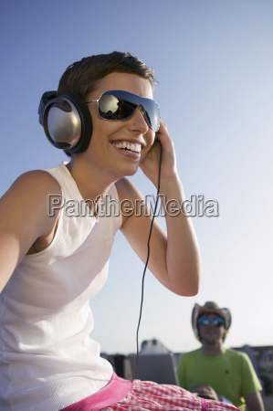 young woman listening to music while