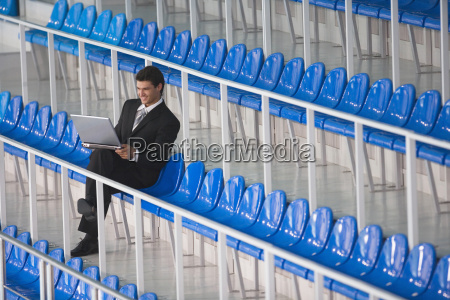man sitting on tribune using laptop