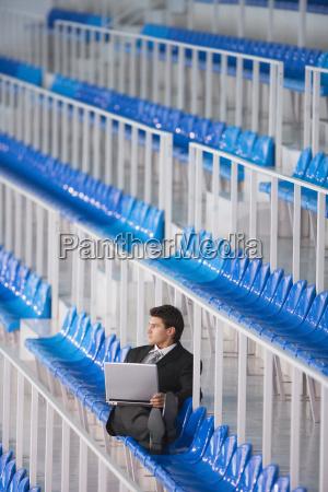 man sitting on tribune using laptop