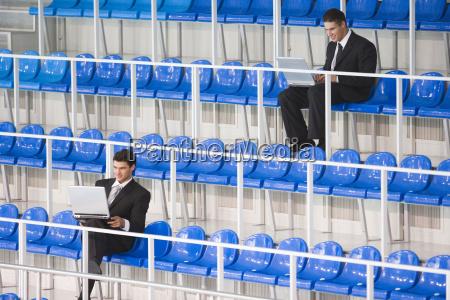 business men sitting on tribune using