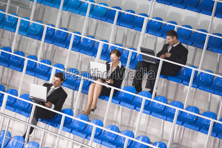 business people sitting on tribune using