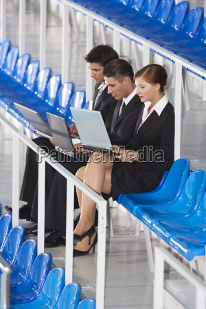 business people sitting on tribune using