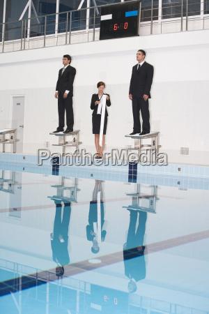 businessmen standing on starting blocks woman