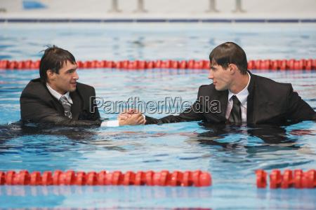wet businessmen shaking hands in pool