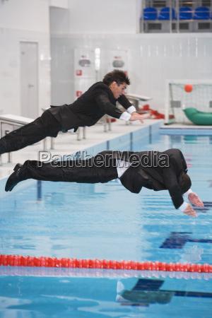 geschaeftsleute springen in pool
