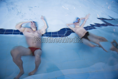 zwei mann im pool unter wasser