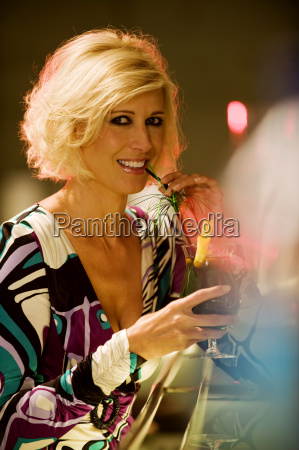 young woman in bar drinking cocktail