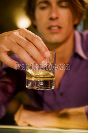 young man in bar holding whiskey