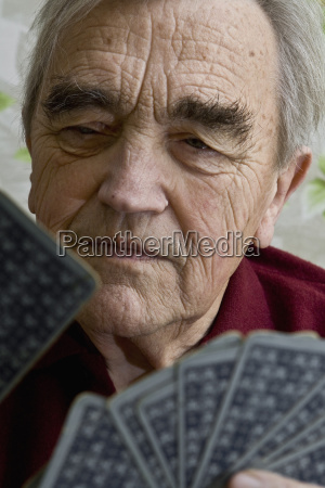 senior man holding and playing cards