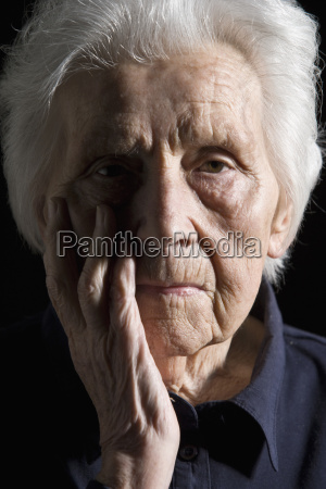 senior woman with head in hand