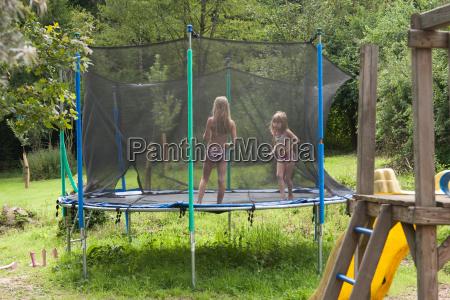 zwei schwestern auf dem trampolin im