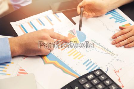 business kollegen diskutieren papierkram und diagramme