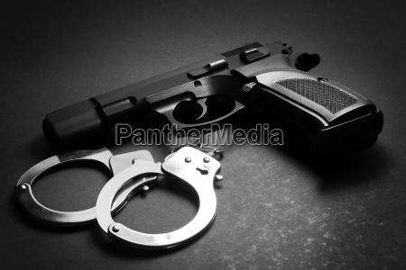 pistole mit handschellen auf dunklem hintergrund