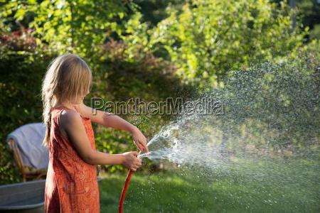 blondes maedchen mit wasserstrahl im gegenlicht