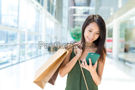 woman holding shopping bag and using