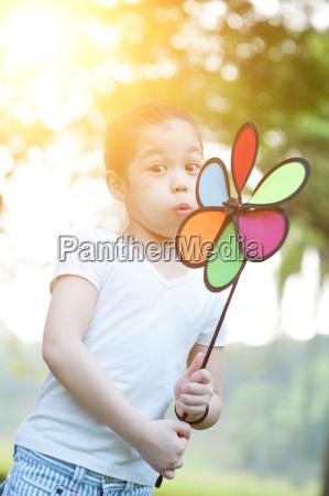 asiatische kind blaest windmuehle im freien
