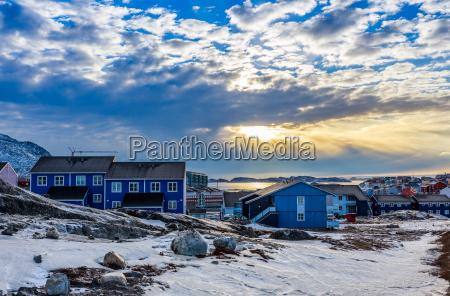 polarer sonnenuntergang ueber inuit haeusern auf