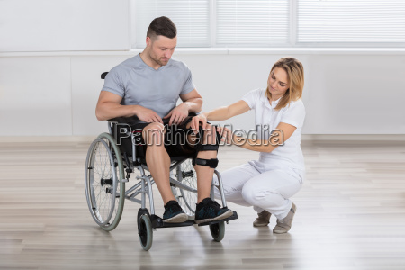 female physiotherapist fixing knee braces on