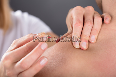 hand putting acupuncture needle on mans